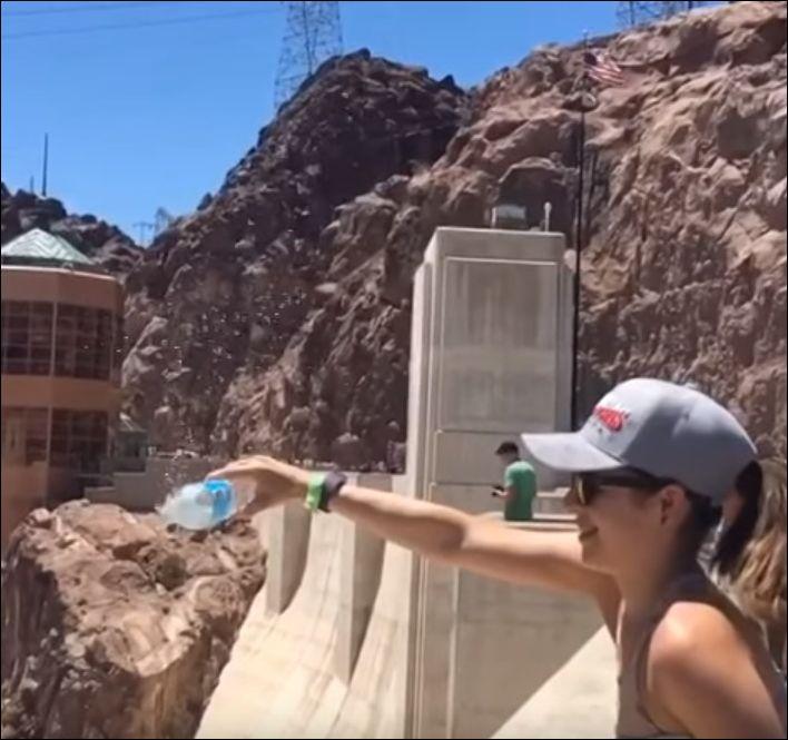 Вода выливается из бутылки вверх из-за сильного воздушного потока