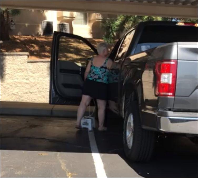 Женщина забирается в высокую машину с помощью табуретки на веревке